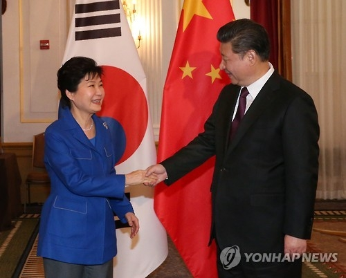 This photo, taken on April 1, 2016, shows President Park Geun-hye (L) shaking hands with Chinese President Xi Jinping before their talks on the sidelines of the Nuclear Security Summit in Washington D.C. (Yonhap)
