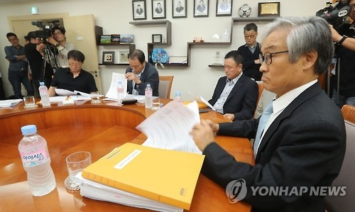Cho Nam-don (R), head of the K League disciplinary committee, reviews documents before meting out punishment on Jeonbuk Hyundai Motors over bribery scandal at the Korea Football Association headquarters in Seoul on Sept. 30, 2016. (Yonhap)