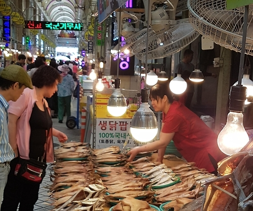 A customer and shopowner (R) appear to be bargaining over the price of some dried fish, a local specialty of Sokcho, Gangwon Province in the photo taken on July 19, 2016. (Yonhap)