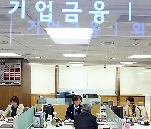 This undated file photo shows bank workers handling corporate financing. (Yonhap)