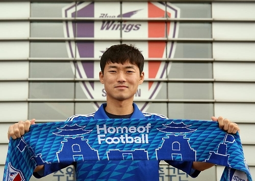 In this photo released by the Suwon Samsung Bluewings on Jan. 11, 2017, South Korean goalkeeper Shin Hwa-yong holds Suwon's scarf after signing a contract with the football club. (Yonhap)