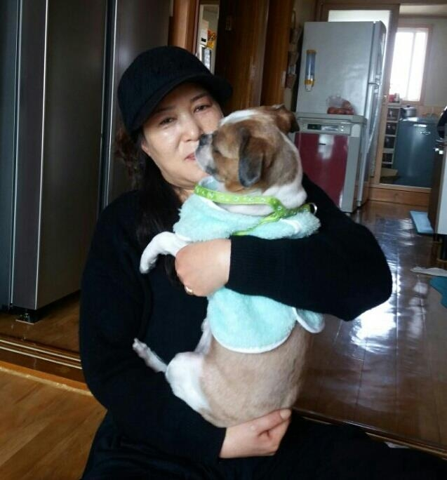 In this photo taken on March 22, 2017, Kim Myeong-seon, a full-time housewife, hugs her companion animal Mong at her home in Daegu, about 300 kilometers southeast of Seoul, after it underwent hernia surgery last week. (Yonhap)