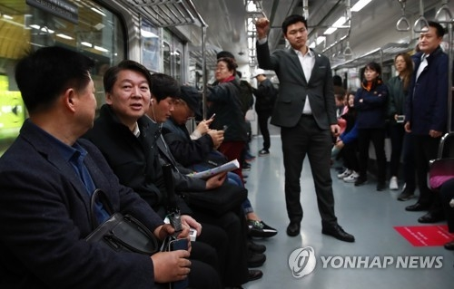 Ahn Cheol-soo (2nd from L), the presidential nominee of the centrist People's Party, talks to a passenger on the subway in Seoul on April 5, 2017. (Yonhap)