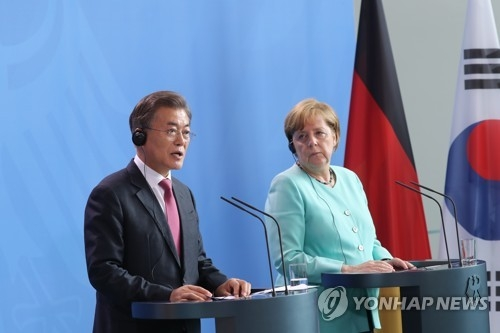 South Korean President Moon Jae-in (L) and German Chancellor Angela Merkel hold a joint press conference shortly before the start of their bilateral summit in Berlin on July 5, 2017. (Yonhap)