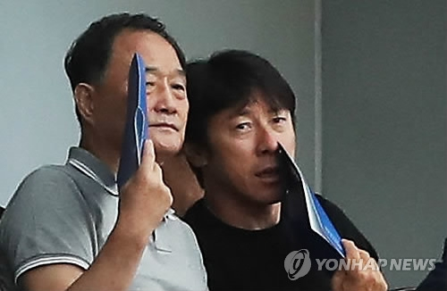 South Korea's national football team head coach Shin Tae-yong (R) speaks with the Korea Football Association technical director Kim Ho-gon during the K League Classic match between Suwon Samsung Bluewings and Jeju United at Suwon World Cup Stadium in Suwon, Gyeonggi Province, on July 9, 2017. (Yonhap)