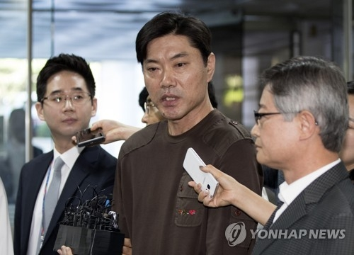 Choi Kyu-soon (C), a former baseball umpire accused of taking money from professional clubs, speaks to reporters before attending a hearing on his arrest warrant at Seoul Central District Court on Sept. 1, 2017. (Yonhap)
