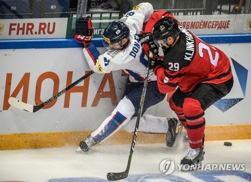In this AFP photo, Canadian forward Rob Klinkhammer (R) battles South Korean defenseman Lee Don-ku during the teams' Channel One Cup game at VTB Ice Palace in Moscow on Dec. 13, 2017. (Yonhap)