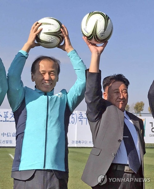 This file photo shows Gangwon Governor Choi Moon-soon (L) and Mun Ung, the chairman of the North's April 25 Athletic Committee, posing for a photo at an international youth football championship in the Chinese city of Kunming in late December of 2017. (Yonhap)