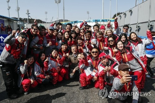 This photo provided by South Korea's presidential office shows South Korean President Moon Jae-in (C) taking a photo with volunteers at the PyeongChang Winter Paralympics at Alpensia Biathlon Centre in PyeongChang, Gangwon Province, on March 14, 2018. (Yonhap)