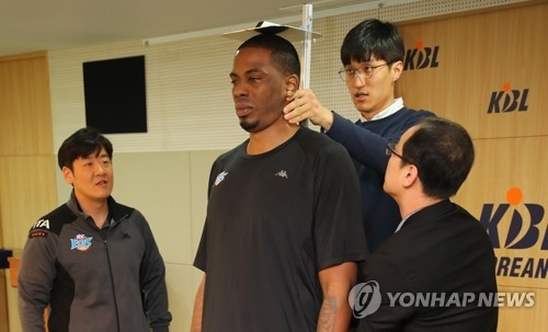 In this file photo taken April 6, 2018, Korean Basketball League (KBL) officials measure the height of Jeonju KCC Egis player Charles Rhodes (C) at the KBL Center in Seoul. (Yonhap)