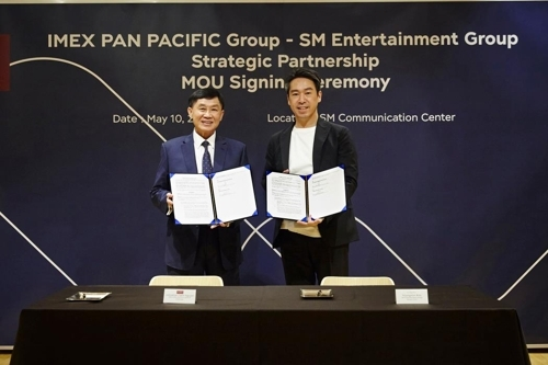 In this photo provided by SM Entertainment, IPP Group Chairman Johnathan Hanh Nguyen (L) and Kim Young-min, CEO of SM Entertainment, pose for the camera after singing a memorandum of understanding in Seoul on May 10, 2018. (Yonhap)