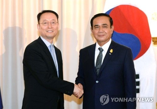 Paik Un-gyu, South Korean minister of trade, industry and energy (L), shakes hands with Thailand's Prime Minister Prayuth Chan-ocha (R) after their meeting in Bangkok on May 16, 2018, in this photo provided by the ministry. (Yonhap)