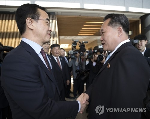 This photo, taken by the Joint Press Corps on June 1, 2018, shows South Korea's chief delegate Cho Myoung-gyon (L) shaking hands with his North Korean counterpart Ri Son-gwon during high-level talks held at the truce village of Panmunjom. (Yonhap)