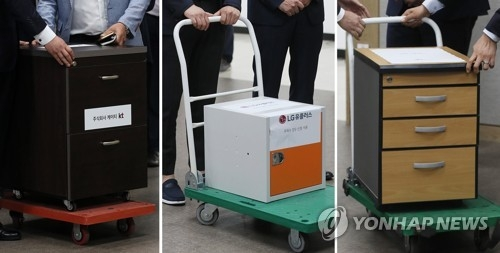 Photos show officials from South Korea's three mobile carriers -- KT Corp. LG Uplus Inc. and SK Telecom Co. (L to R) -- pushing carts to submit their application documents for the country's first auction for high-end fifth-generation network frequencies with the Ministry of Science and ICT on June 4, 2018. (Yonhap)