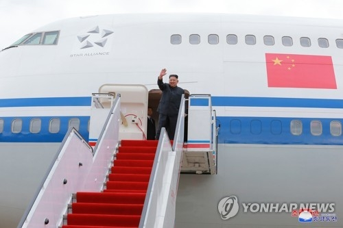 A June 11, 2018, photo in the Rodong Sinmun shows North Korean leader Kim Jong-un waving to well-wishers at a Pyongyang airport before boarding an Air China plane featuring the Chinese national flag. (Yonhap)