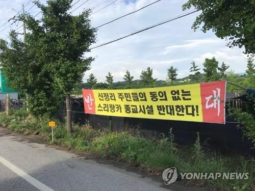 Shown in the file photo taken July 12, 2018, is a banner protesting the planned construction of a Sri Lankan temple in Sinjeongri, Asan. (Yonhap)