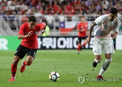 South Korea's Hwang Hee-chan (L) dribbles against Chile's Guillermo Maripan during a friendly football match at Suwon World Cup Stadium in Suwon, south of Seoul, on Sept. 11, 2018. (Yonhap)