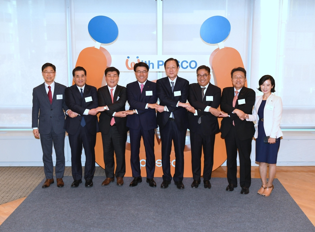 In this photo taken on Nov. 30, 2018, POSCO CEO Choi Jeong-woo (4th from left) holds hands with officials from subcontractors of POSCO Group's five affiliates in an event held at POSCO Center, southern Seoul. (Yonhap)