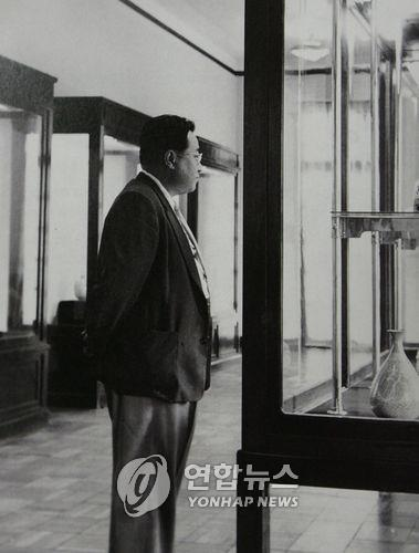 In this old image, Jeon Hyeong-pil, founder of Kansong Art Museum, looks at his art collection. (Yonhap)