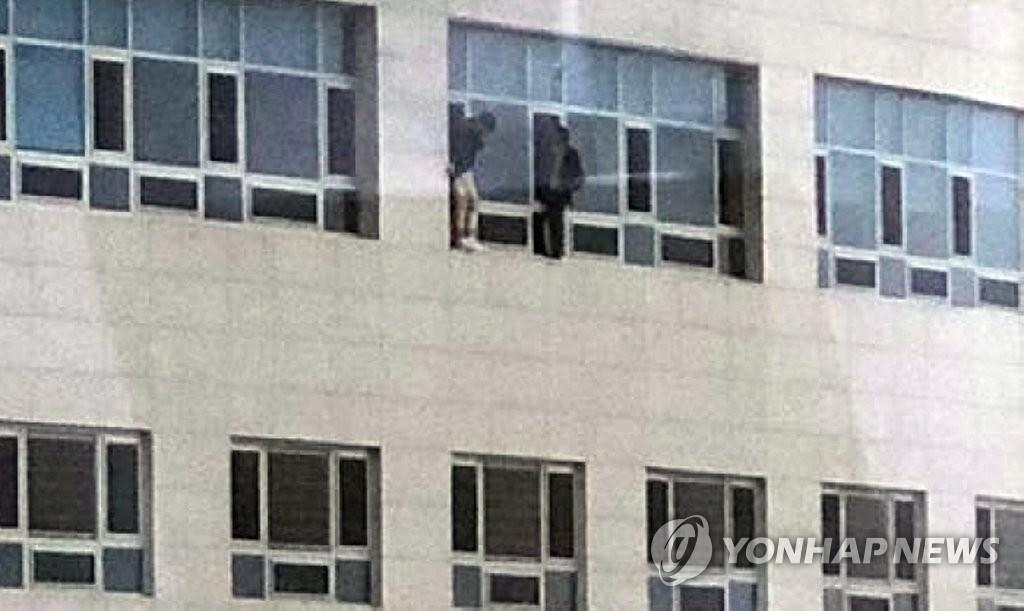 Two individuals wait for rescue from the Ramada Encore Cheonan hotel in Cheonan, South Chungcheong Province, on Jan. 14, 2019, in this photo provided by a citizen, Kim Soo-young. (Yonhap)