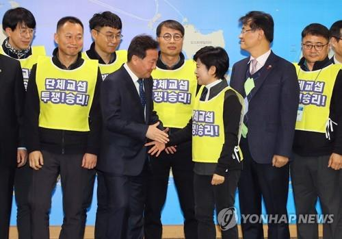 Minister of Personnel Management Hwang Seo-chong (4th from L) shakes hands with a representative of civil servant unions after signing a collective bargaining agreement at the Sejong Government Complex on Jan. 21, 2019. (Yonhap)