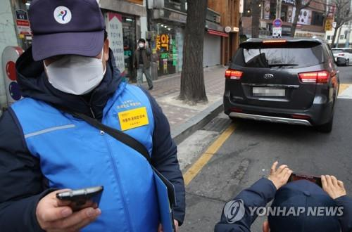 This file photo taken on Jan. 15, 2019, shows employees of the Seoul Metropolitan Government cracking down on an idling diesel car after emergency anti-fine dust measures were declared in the capital area. (Yonhap)