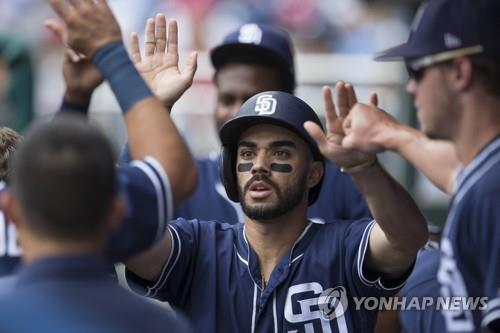 In this Getty Images file photo from July 22, 2018, Carlos Asuaje, then of the San Diego Padres, celebrates with his teammates in the dugout after scoring a run in the top of the first inning against the Philadelphia Phillies at Citizens Bank Park in Philadelphia. (Yonhap)