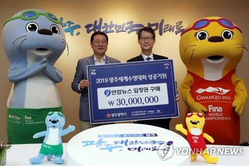 Gwangju Mayor Lee Yong-seop (L) and Yonhap News CEO Cho Sung-boo pose at Gwangju City Hall on June 7, 2019, during a ceremony marking Yonhap's purchase of tickets for the 2019 FINA World Championships. (Yonhap)