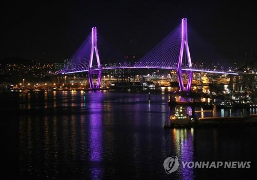 This photo taken June 13, 2019, shows Busan Harbor Bridge illuminated in violet ahead of BTS' first live solo performance in the city. (Yonhap)