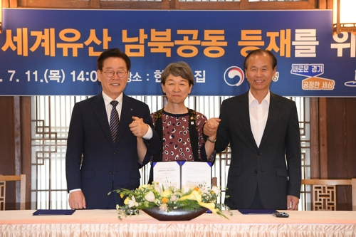 Chung Jae-suk (C), chief of the Cultural Heritage Administration, Gyeonggi Gov. Lee Jae-myung (L) and Gangwon Gov. Choi Moon-soon pose for a photo after signing an agreement in Seoul on July 11, 2019, to work together toward the goal of having the Demilitarized Zone listed on the UNESCO World Heritage List with the cooperation of North Korea. (Yonhap)