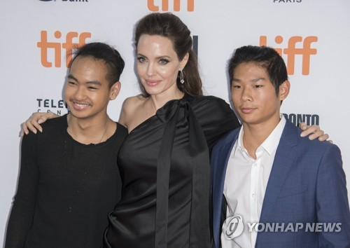This file photo shows Angelina Jolie (C) and her sons, Maddox Jolie-Pitt (L) and Pax Jolie-Pitt, attending the Toronto International Film Festival in Toronto, Canada, on Sept. 11, 2017. (EPA-Yonhap)