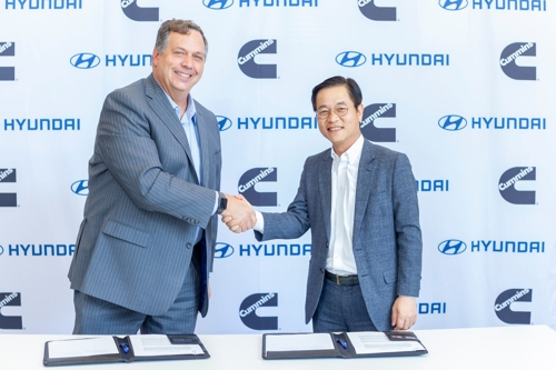 In this undated photo provided by Hyundai Motor, Hyundai Motor Vice President Kim Sae-hoon (R), head of the carmaker's fuel cell business, and Cummins Vice President Thad Ewald shake hands after signing a memorandum of understanding for collaboration on hydrogen fuel-cell technology. (PHOTO NOT FOR SALE) (Yonhap)