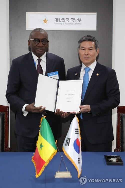 South Korean Defense Minister Jeong Kyeong-doo (R) and his Senegalese counterpart Sidki Kaba pose for a picture after signing a memorandum of understanding on the strengthening of the bilateral defense ties, in Seongnam, Gyeonggi Province, on Oct. 15, 2019, in this photo provided by the Korea Defense Daily. (PHOTO NOT FOR SALE) (Yonhap)