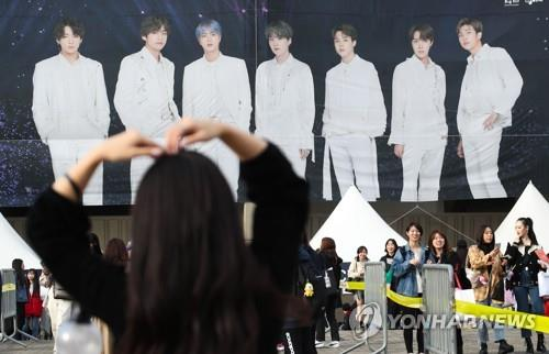 A BTS fan poses in front of an image of the band inside an event zone on the sidelines of a BTS concert in Seoul on Oct. 26, 2019. (Yonhap)