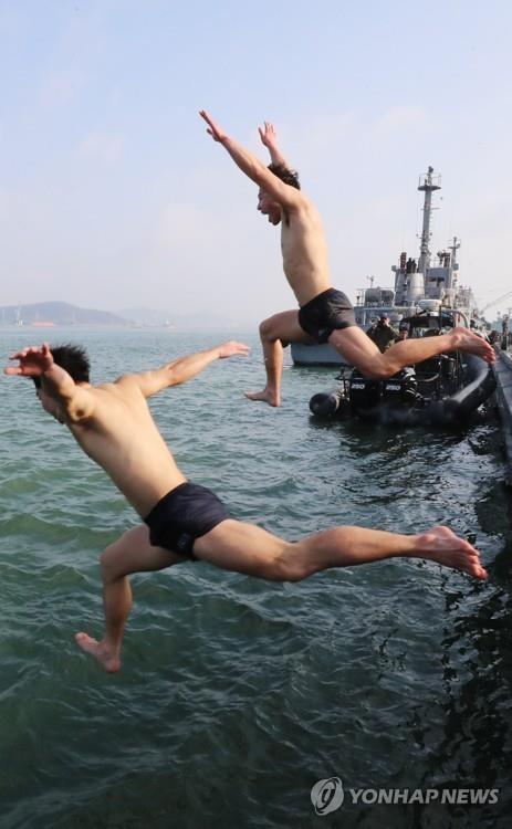 Members of the Navy's elite ship salvage unit (SSU) jump into cold water in the sea off Yeongam on the southwestern coast on Jan. 17, 2018, as part of their cold weather exercise. (Yonhap)