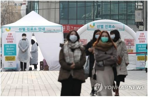 People wearing masks walk past a novel coronavirus screening clinic in Myeongdong in downtown Seoul on Feb. 2, 2020. (Yonhap)