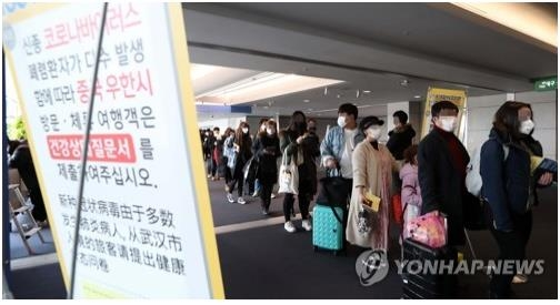 People wearing masks wait in line to go through quanantine at Incheon International Airport on Jan. 28, 2020. (Yonhap)