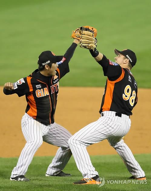 In this file photo from Oct. 13, 2017, Andy Burns (R) and Shin Bon-ki of the Lotte Giants celebrate their 7-1 victory over the NC Dinos in Game 4 of the Korea Baseball Organization first round playoff series at Masan Stadium in Changwon, 400 kilometers southeast of Seoul. (Yonhap)