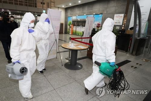 Health officials enter the health ministry in Sejong on March 7, 2020, after a public servant working for the ministry was diagnosed with COVID-19. (Yonhap)