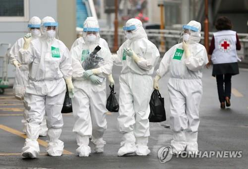 Medical professionals wearing protective gear are seen walking into a hospital in South Korea's southeastern city of Daegu on March 27, 2020. (Yonhap)