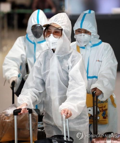 Passengers in protective gear arrive at Incheon airport, west of Seoul, on April 3, 2020, on a flight from the northeastern Chinese city of Qingdao amid concern about the spread of the new coronavirus. (Yonhap)
