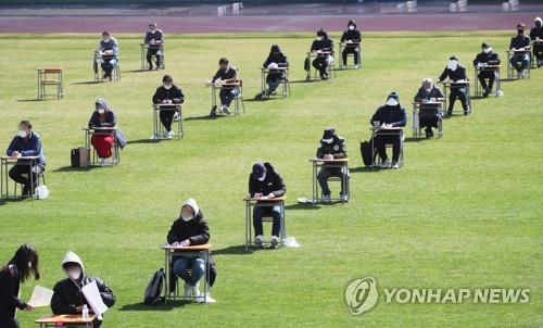 More than 100 job applicants, seated at a safe distance from one another, take a written exam as part of the recruitment process at the city-run Ansan Urban Corp. at a football stadium in Ansan, about 40 kilometers south of Seoul, on April 4, 2020. The urban planning firm decided to hold the test outdoors to prevent the spread of the coronavirus. (Yonhap)