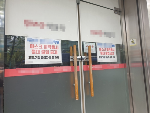 "A signboard reading ""No access without face masks"" is posted on the gate of a cram school in Dongjak Ward, southern Seoul as it resumed operations on April 20, 2020, amid relaxed social distancing rules. (Yonhap)"