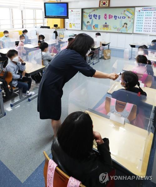 A teacher checks students' temperatures at Hanil Elementary School in the city of Suwon, south of Seoul, on May 27, 2020, amid the coronavirus pandemic. (Yonhap)