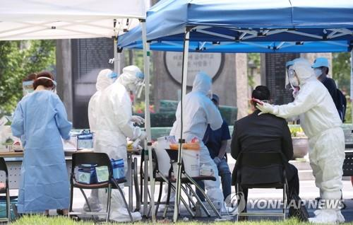 This photo, taken on May 29, 2020, shows medical workers collecting samples from people for new coronavirus tests at a temporary clinic in central Seoul. (Yonhap)