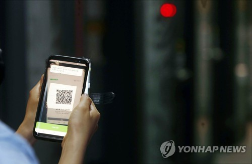 A local government official from Gwangju, 330 kilometers south of Seoul, checks if QR code logs are working at a karaoke establishment on June 9, 2020, in this photo provided by the government office of Buk Ward. (PHOTO NOT FOR SALE) (Yonhap)