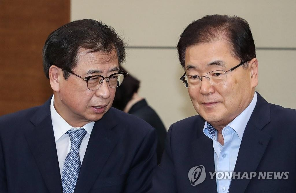 This file photo shows Chung Eui-yong (R), director of national security at Cheong Wa Dae, talking with National Intelligence Service Director Suh Hoon. (Yonhap)