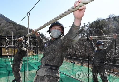 In this file photo, taken on March 13, 2020, and provided by the Navy, recruits undergo combat training while wearing masks at a boot camp of the Naval Education and Training Command in the southeastern city of Changwon amid the nationwide spread of the coronavirus. (PHOTO NOT FOR SALE) (Yonhap)
