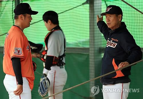 In this file photo from Feb. 28, 2015, Hanwha Eagles' manager Kim Sung-keun (R) speaks with his relief pitcher Song Chang-sik during spring training at Kochinda Baseball Field in Yaese, Okinawa, Japan. (Yonhap)