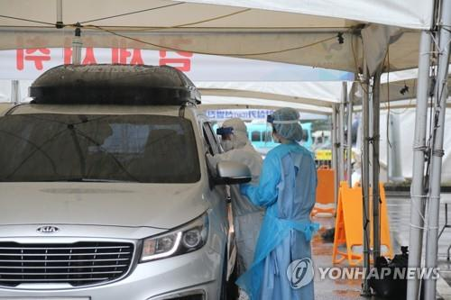 Medical staff members carry out new coronavirus tests at a drive-thru clinic in Goyang, north of Seoul, on Aug. 9, 2020. (Yonhap)